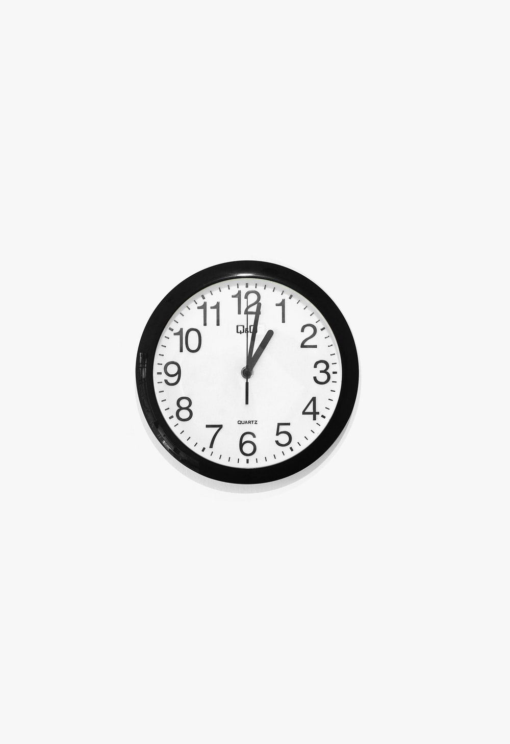 black and white round analog wall clock at 10 10