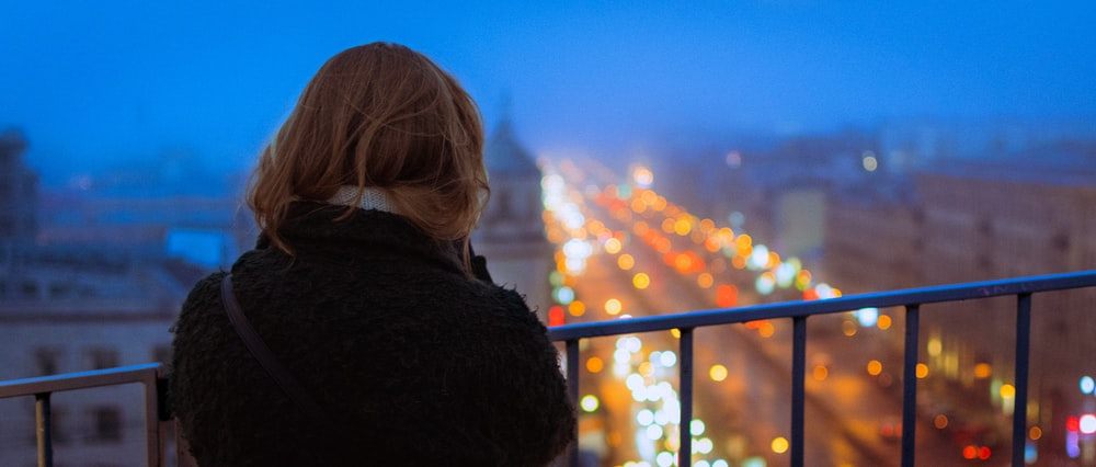 woman in black jacket looking at the city during sunset