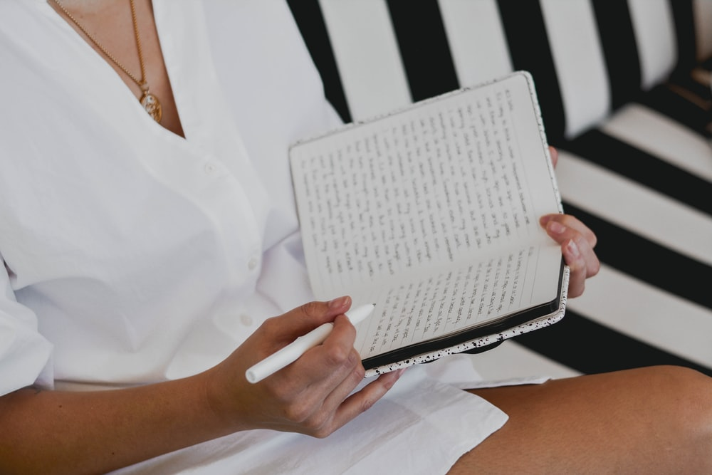 woman in white button up shirt holding white braille paper