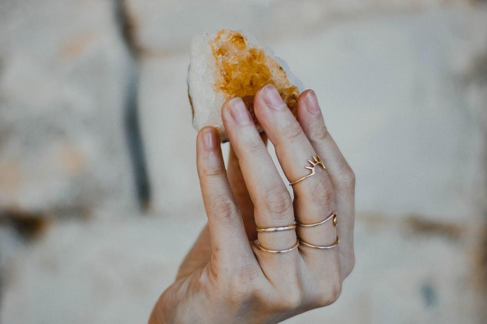 person holding bread with white cream
