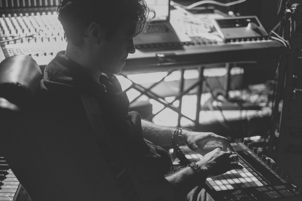 grayscale photo of man in black jacket playing computer