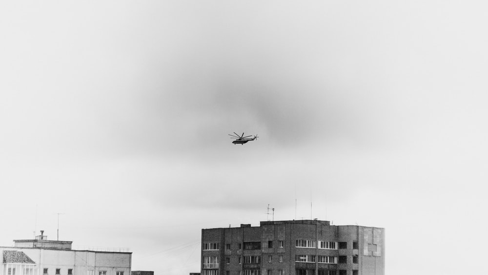 grayscale photo of airplane flying over city buildings