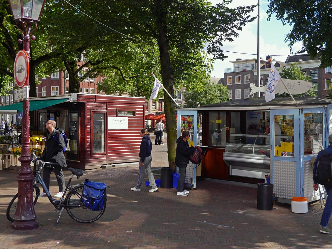 Cozy square in Amsterdam old city with people eating and walking in the street. There is a fish stall and a flower stable, and for children a fountain with water jets,coming from out the brick pavement. Free photo of Dutch street view of 10 June 2020. Viskraam op het Haarlemmerplein en bloemenstal; gratis foto Amsterdam,  Fons Heijnsbroek