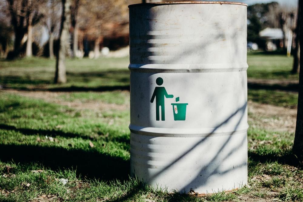 white and green trash bin on green grass field