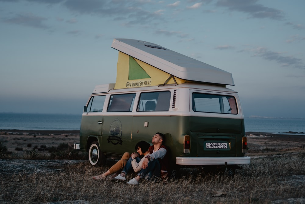 man and woman sitting on ground beside brown van during daytime