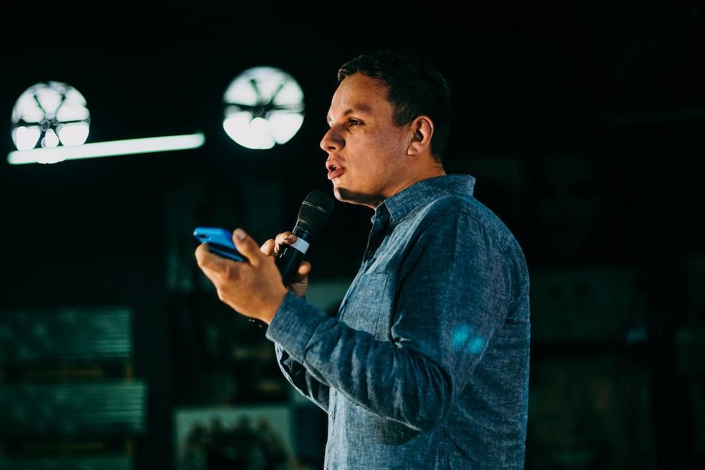 man in blue denim jacket holding microphone