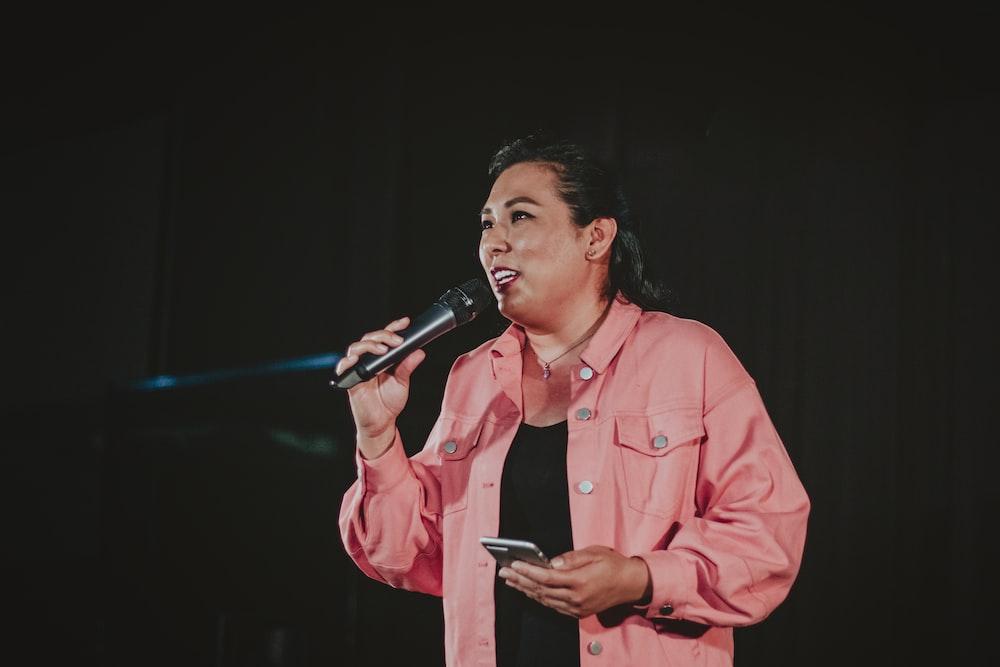 man in pink dress shirt singing