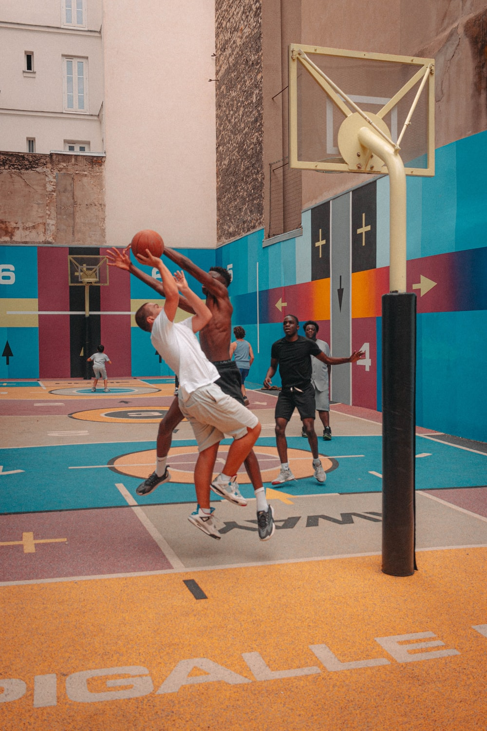 man in white shirt and white shorts playing basketball