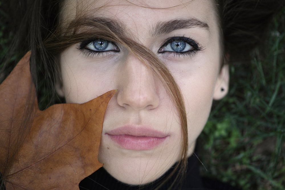 woman in black shirt with brown leaf on her face