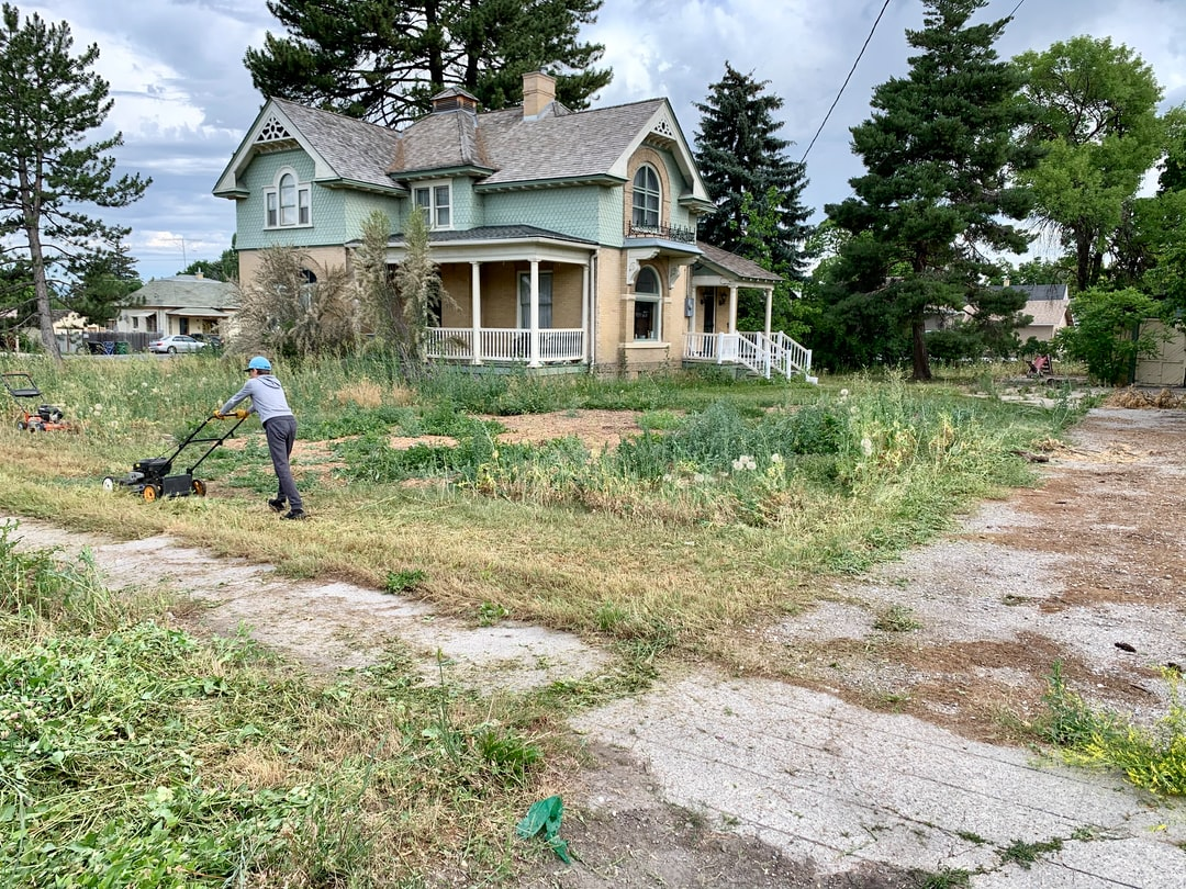 Mowing the lawn and weeds of an old historic home in Smithfield Utah.