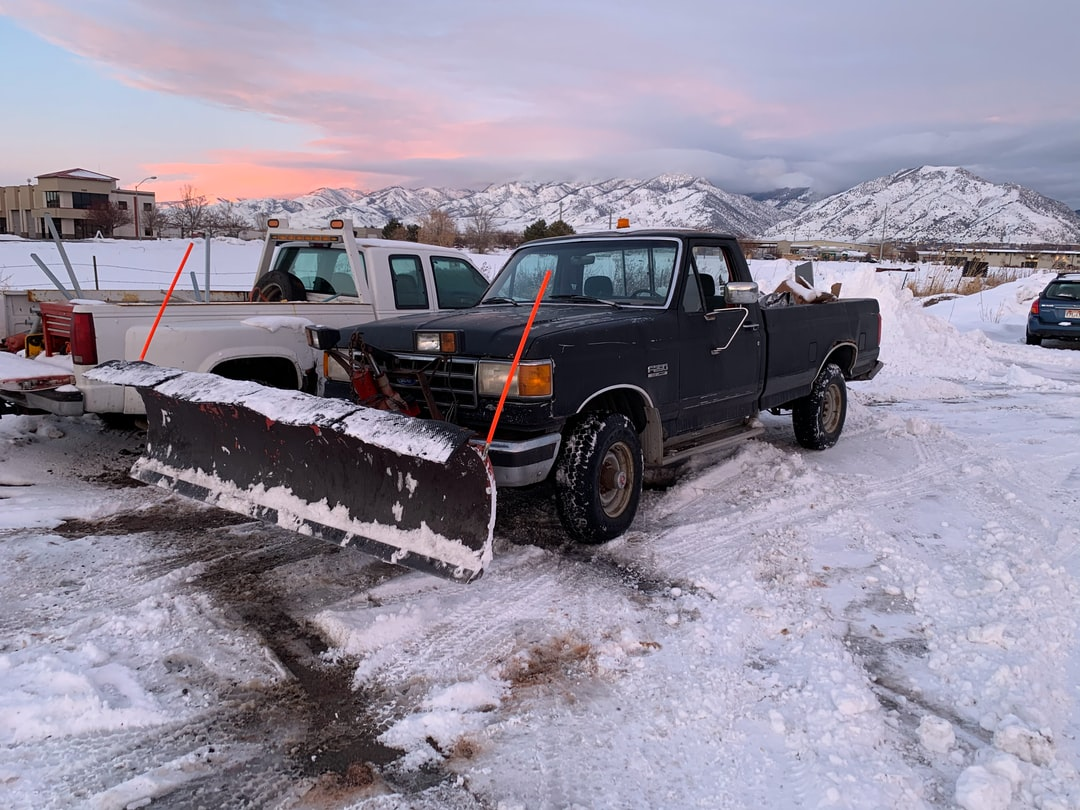 Snow plow truck and sunset