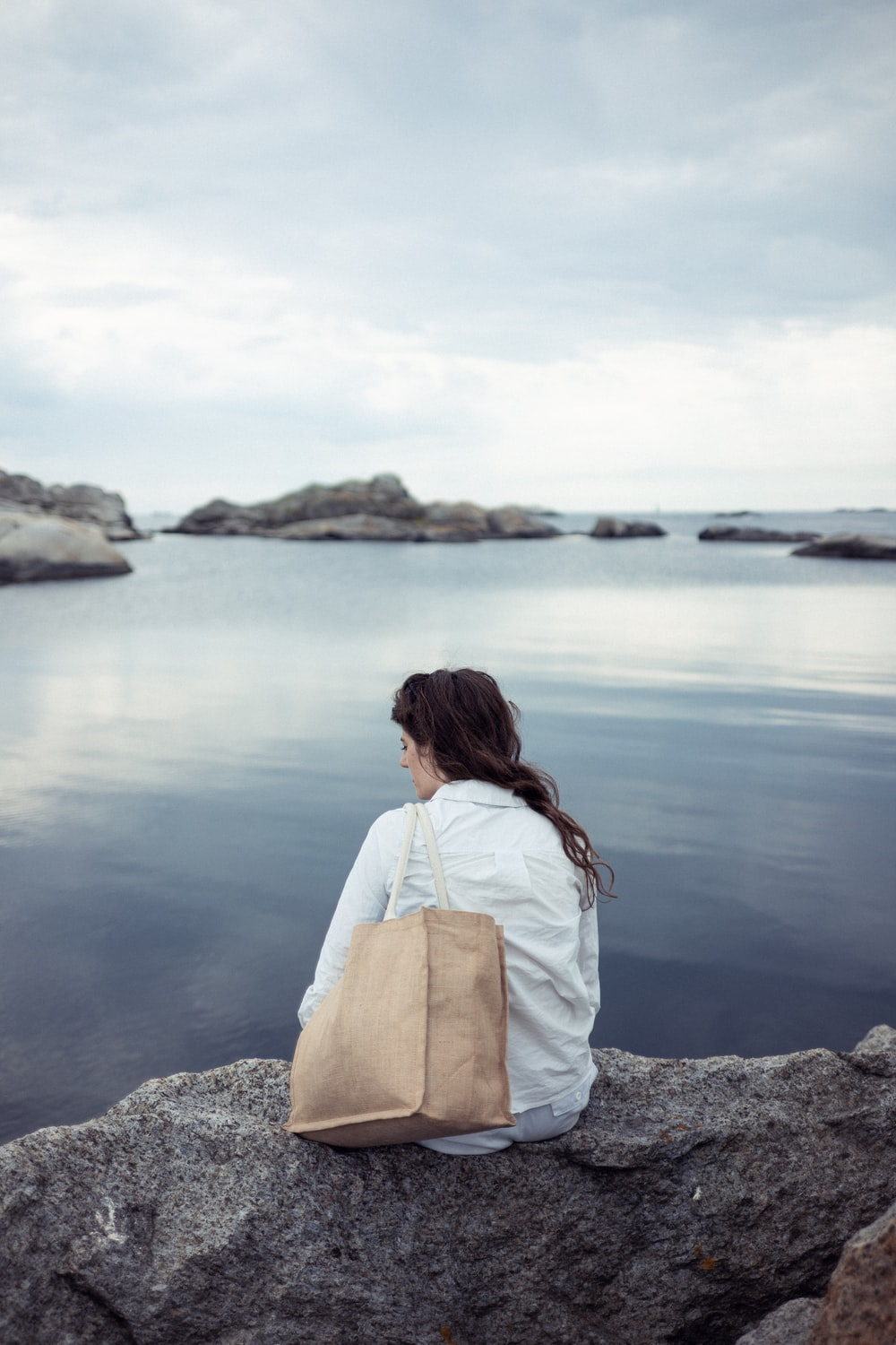 woman in white shirt sitting on rock near body of water during daytime