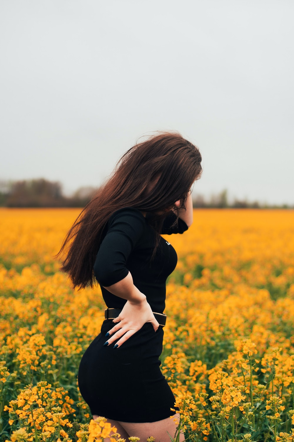 woman in black long sleeve shirt standing on yellow flower field during daytime