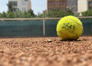 green tennis ball on brown soil during daytime
