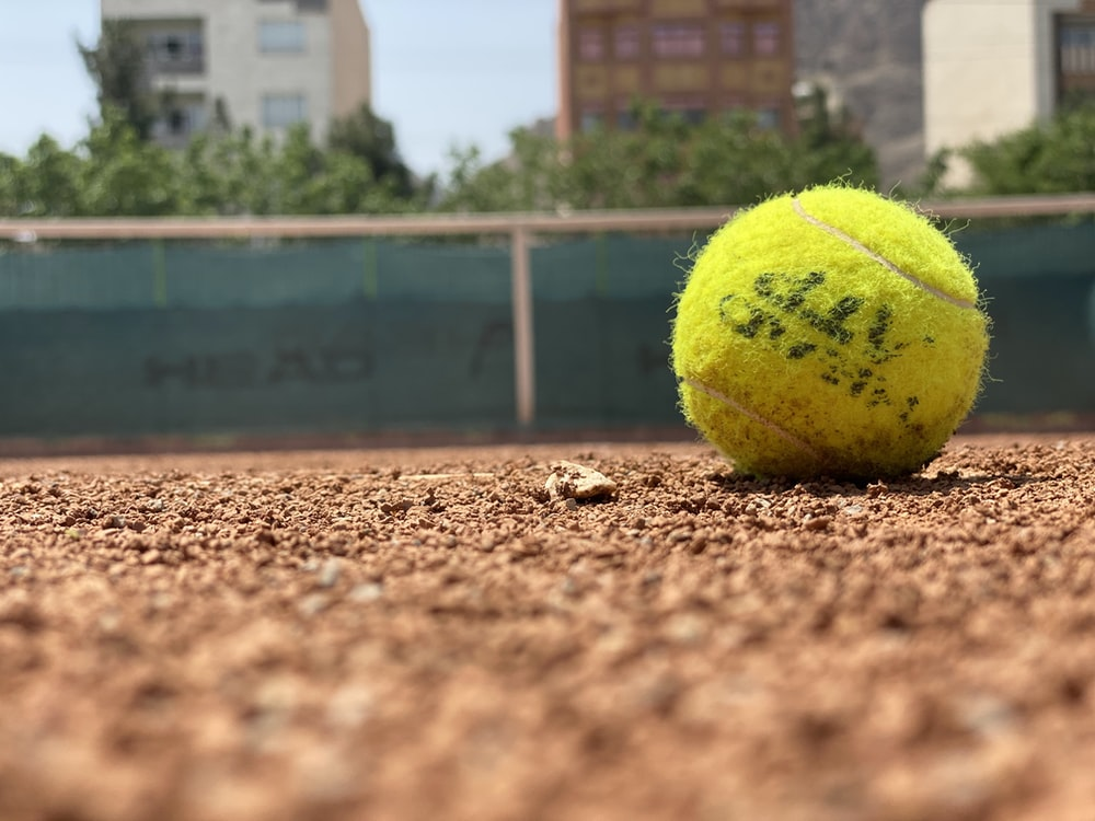 green tennis ball on brown soil during daytime