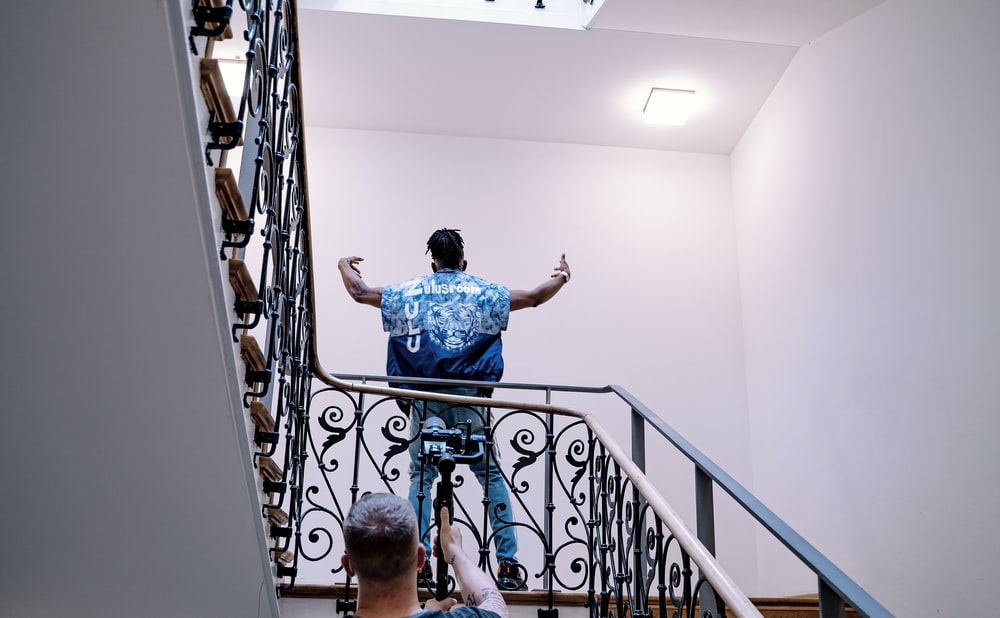 boy in blue t-shirt standing on staircase