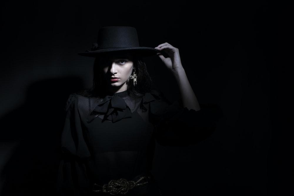 woman in black dress shirt wearing black hat