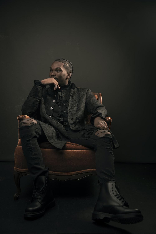 man in black jacket sitting on brown sofa chair