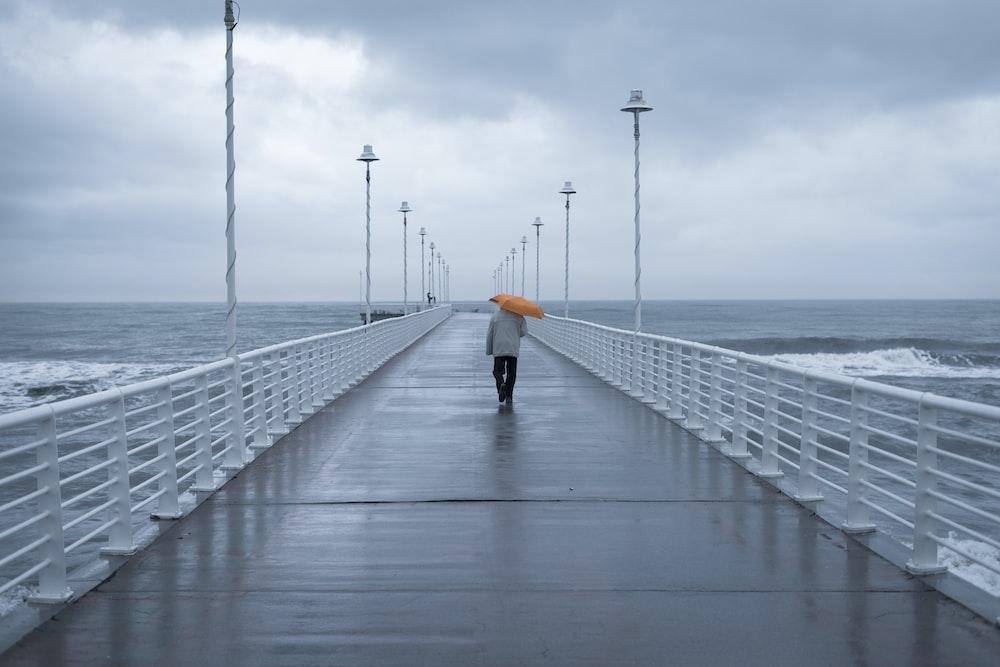 person in black jacket walking on bridge during daytime