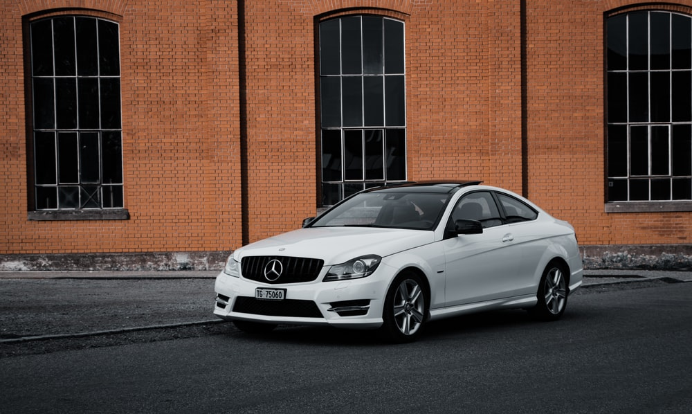 silver mercedes benz coupe parked beside brown brick wall