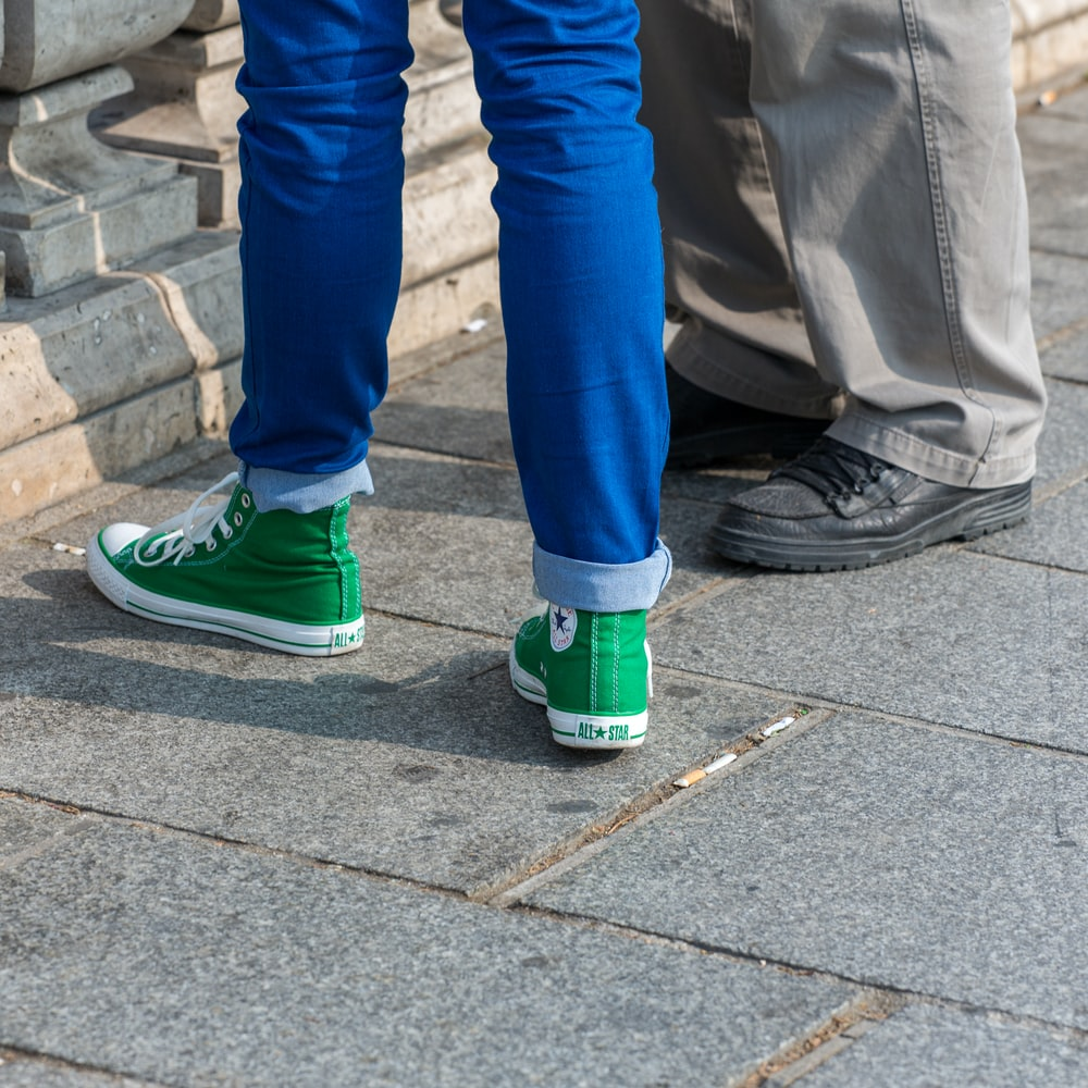 person in blue denim jeans and green nike sneakers