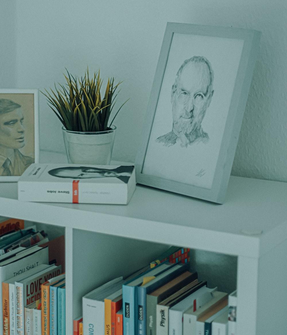 white framed woman portrait on white wooden shelf