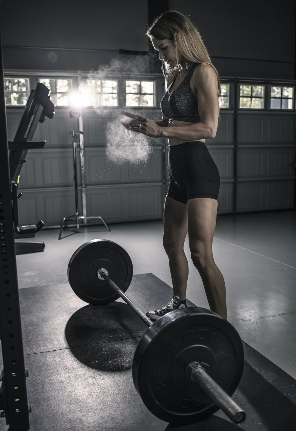 woman in black tank top and black shorts holding barbell