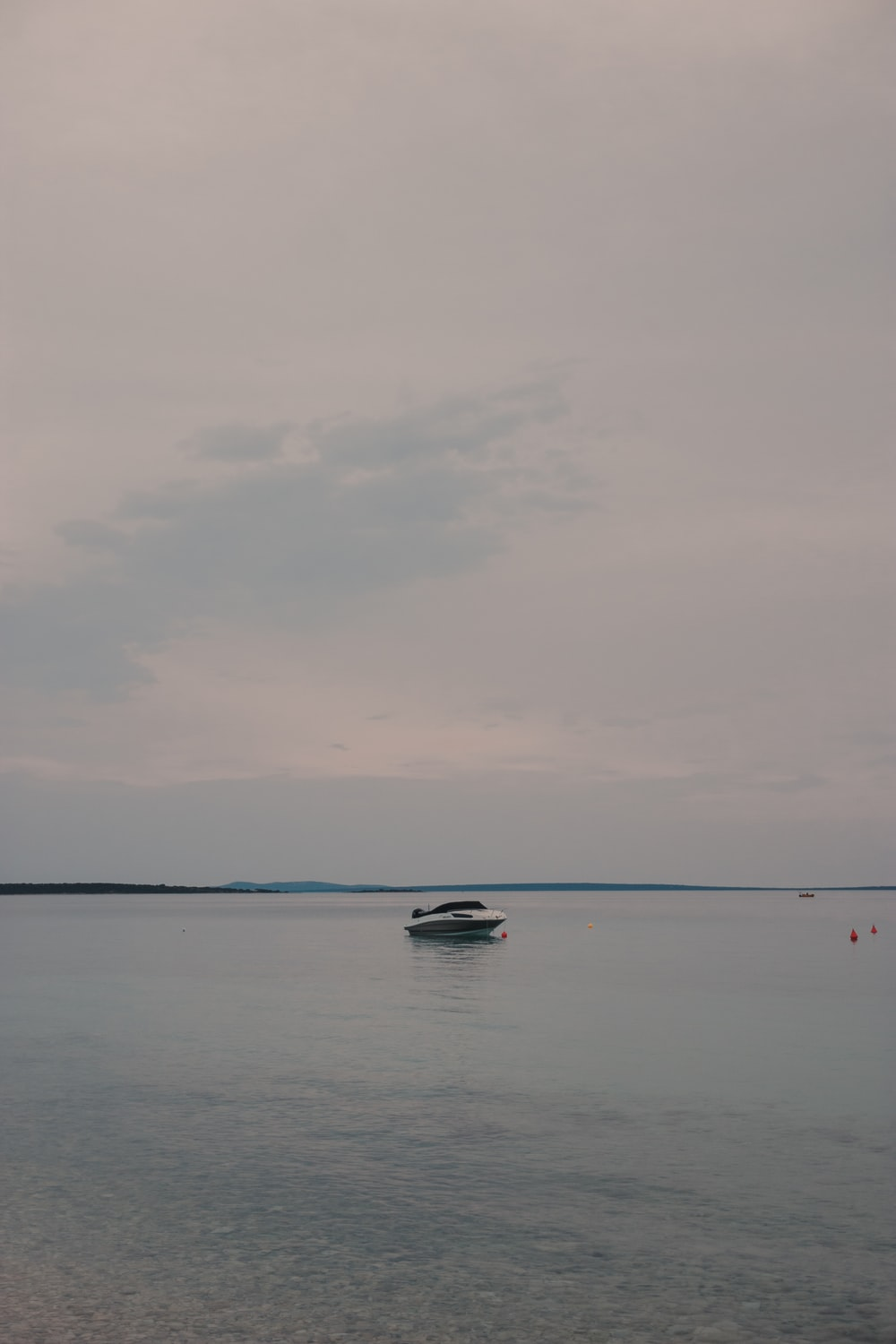 white boat on sea under cloudy sky during daytime