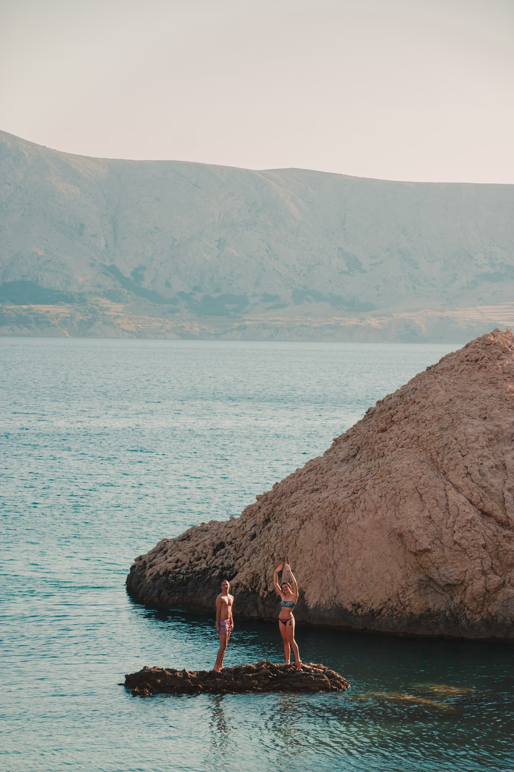 2 women standing on rock near body of water during daytime