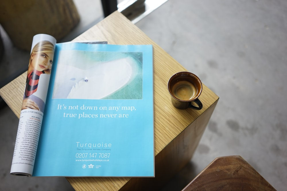 blue and brown book on brown wooden table