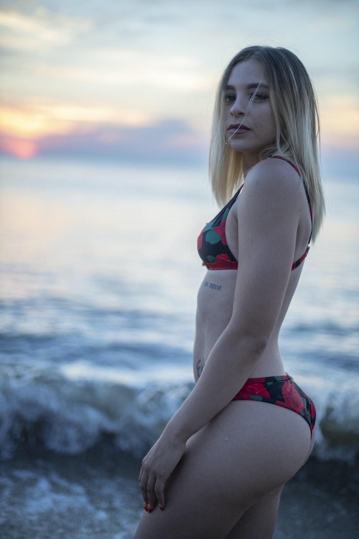 woman in red bikini bottom standing on beach during sunset