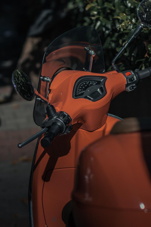 orange and black motorcycle with helmet