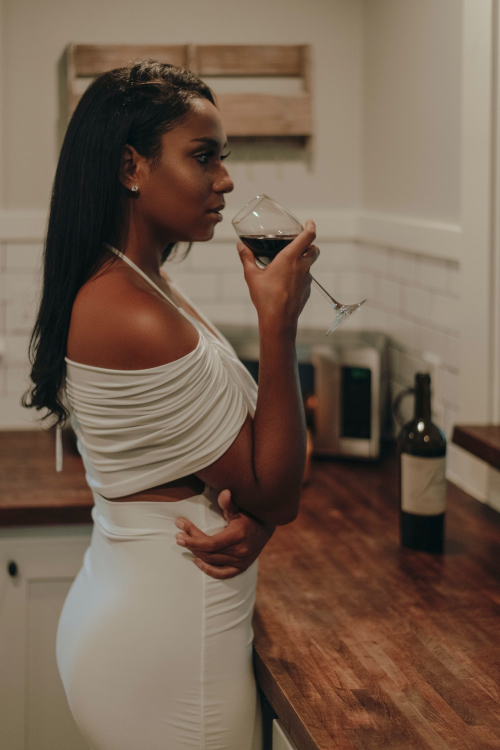 woman in white and black stripe tank top holding clear drinking glass