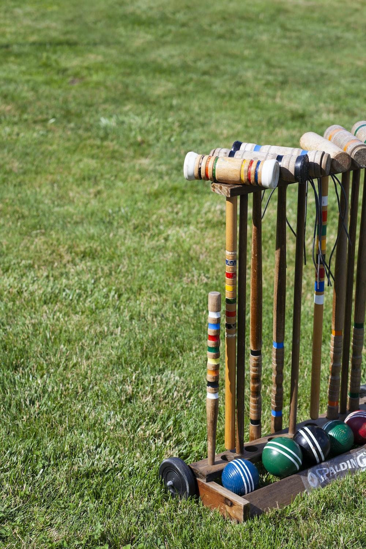 orange and blue wooden sticks on green grass field during daytime