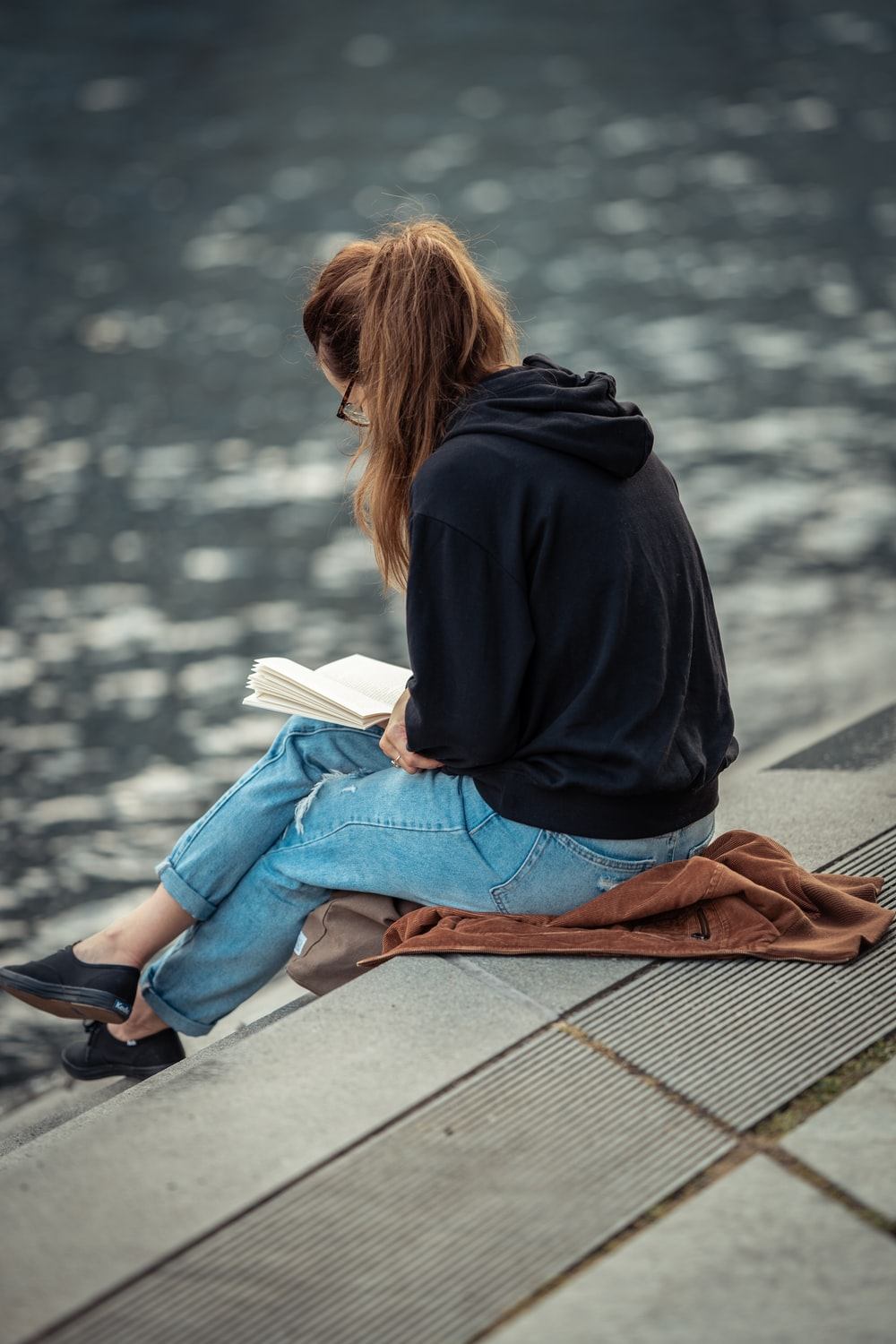 woman in black jacket and blue denim jeans sitting on brown wooden bench reading book