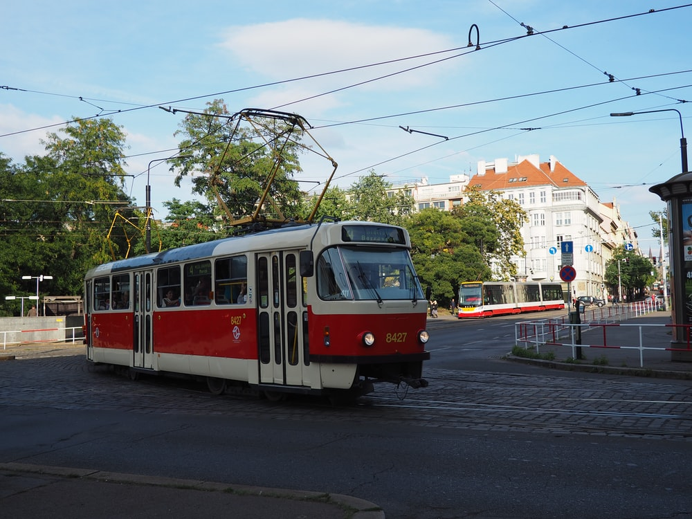 red and white train on the street during daytime