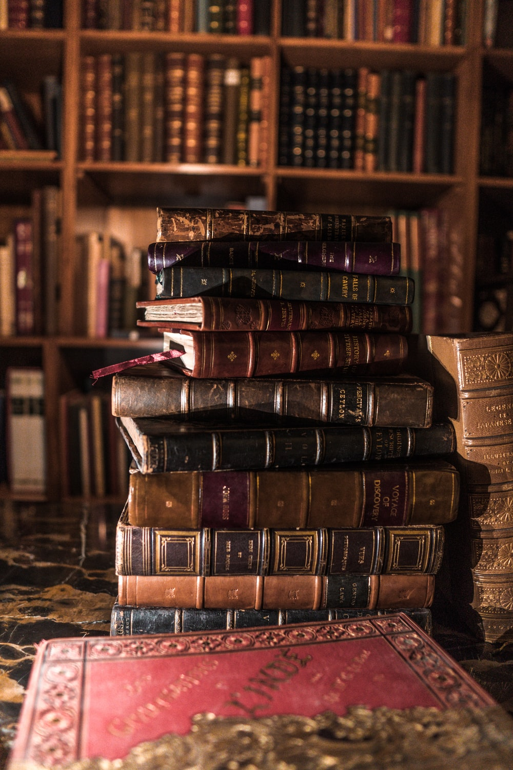 stack of books on brown wooden shelf photo – Free Bookcase Image on Unsplash