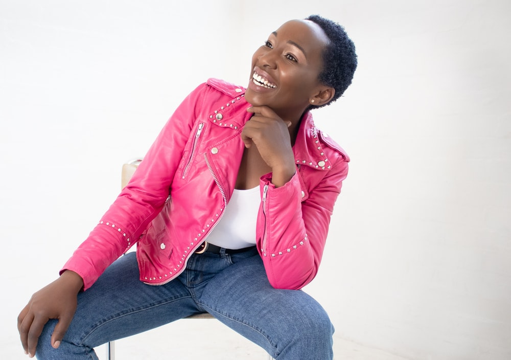 woman in pink leather jacket and blue denim jeans sitting on white floor
