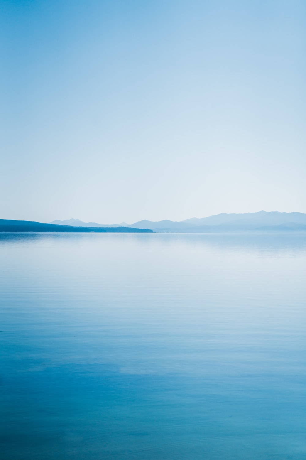 blue body of water under white sky during daytime