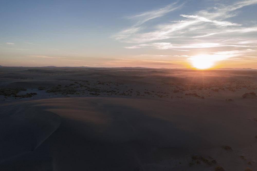 brown sand under blue sky during sunset