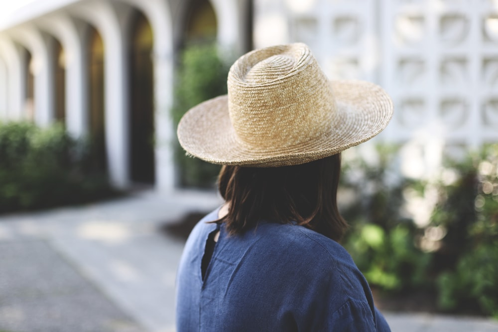woman in blue shirt wearing brown straw hat standing on gray concrete road during daytime