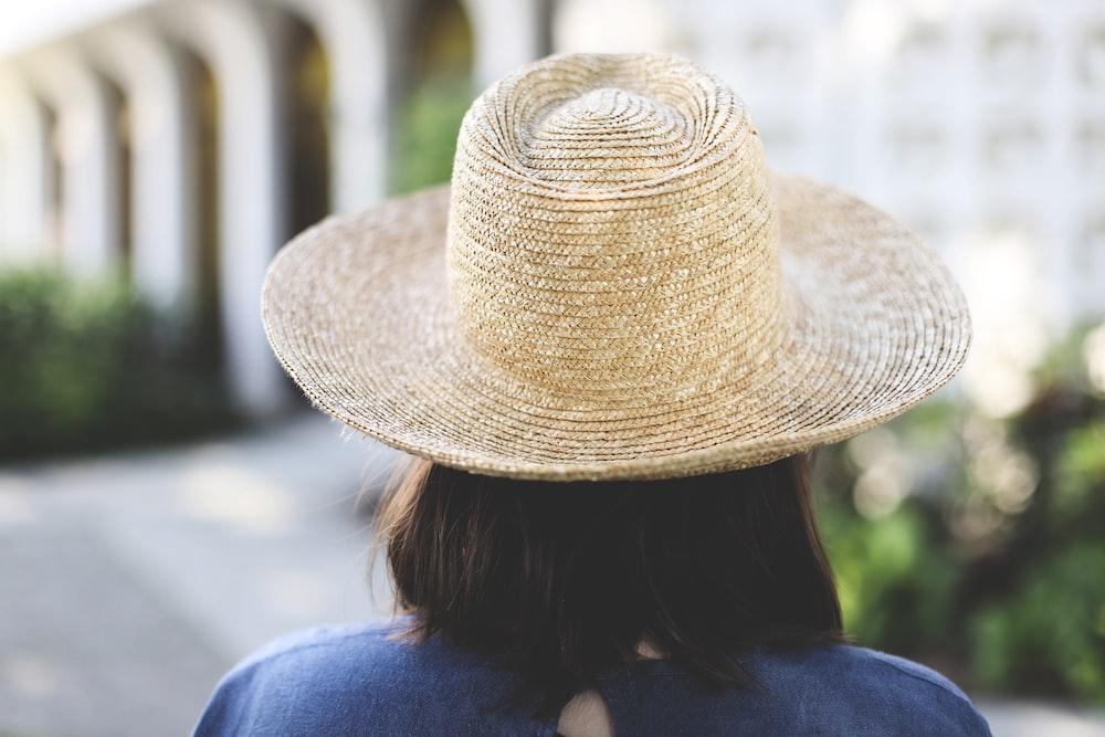 woman in blue shirt wearing brown straw hat