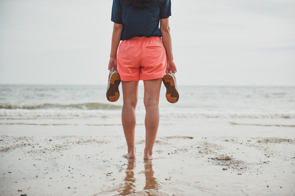 man in blue shirt and orange shorts standing on beach during daytime