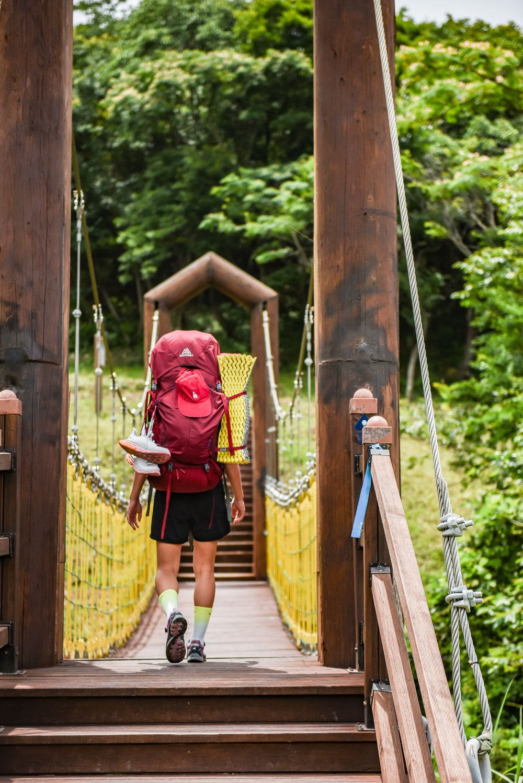 woman in red long sleeve shirt and black skirt walking on hanging bridge
