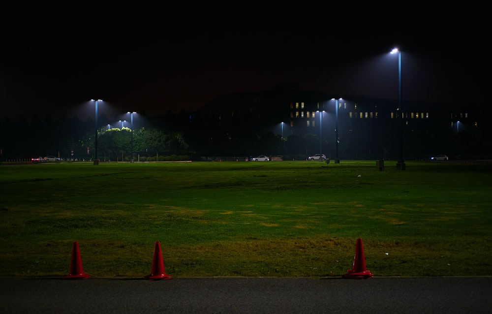 red traffic cone on green grass field during night time