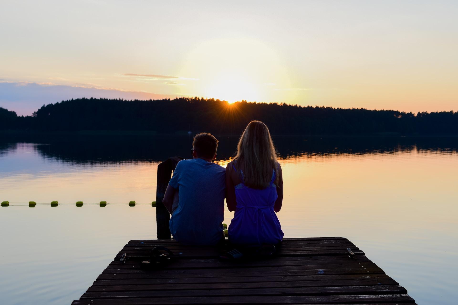 2 women sitting on dock during daytime