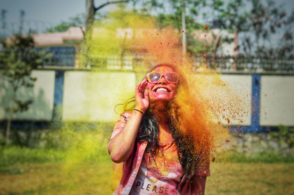 woman in pink tank top with yellow powder on her face