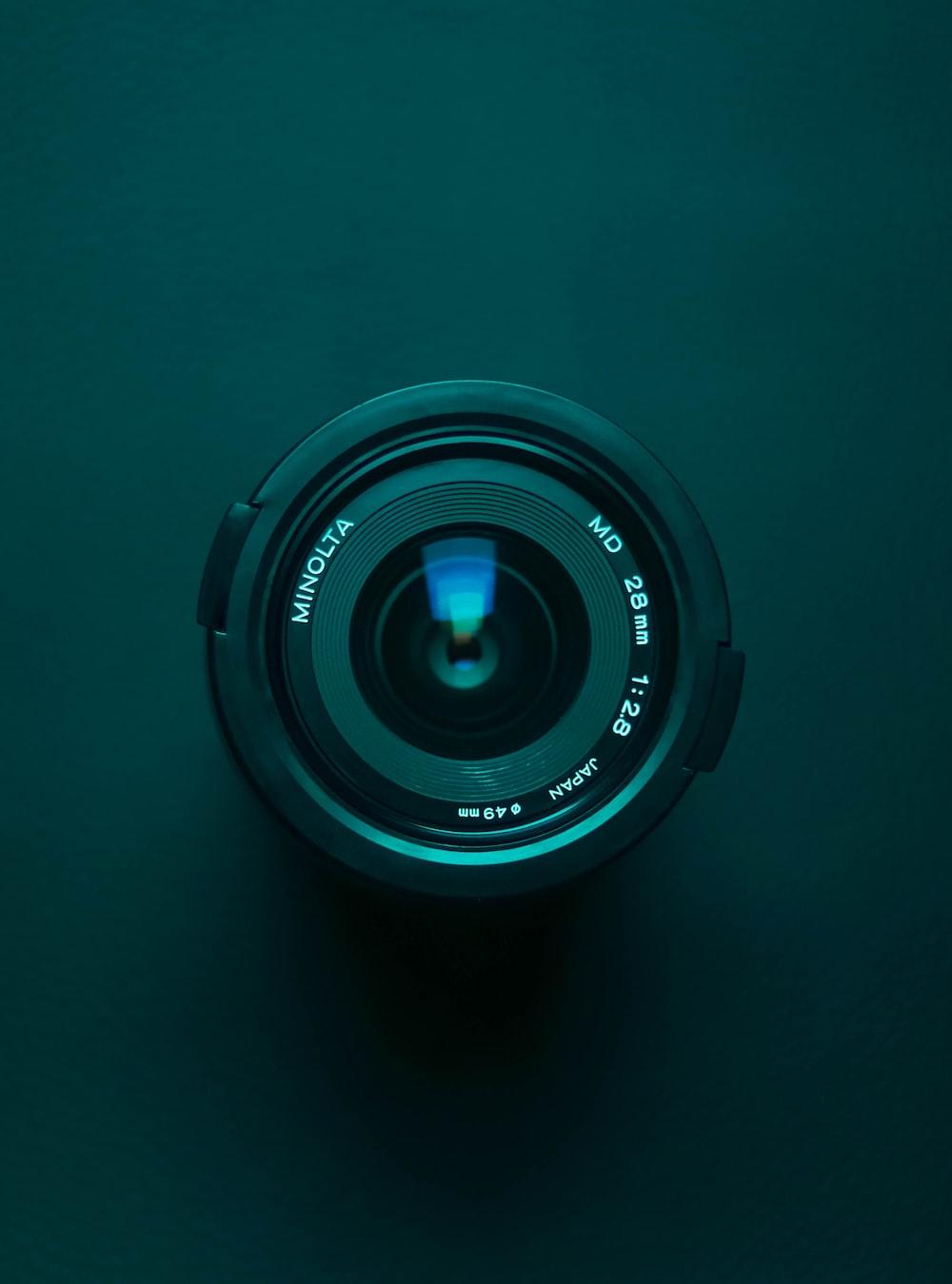 black camera lens on blue surface