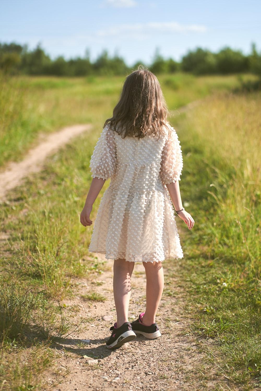 girl in white long sleeve dress walking on green grass field during daytime