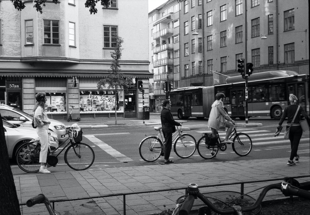 grayscale photo of people riding bicycle on street